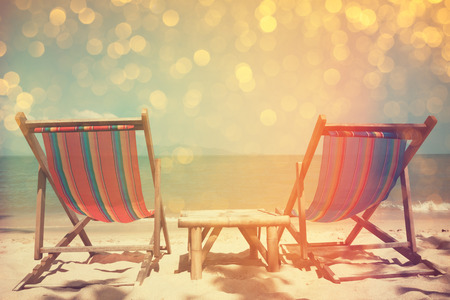 Beach chairs on sea shore with glowing bokeh and film stylized, double exposure effect