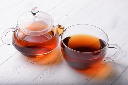 Glas theepot en kopje met hete zwarte thee op een witte houten tafel