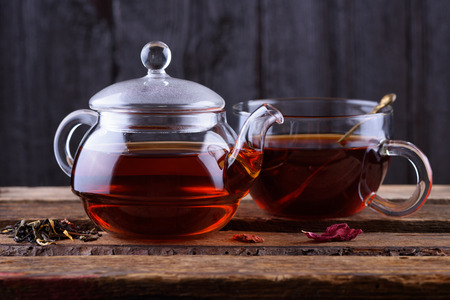 tea table: Glass teapot and cup with hot tea on wooden background Stock Photo
