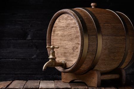 barrels: Vintage oak barrel on rack on old wooden table