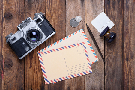 Vintage post card and envelope with retro camera on old wooden table