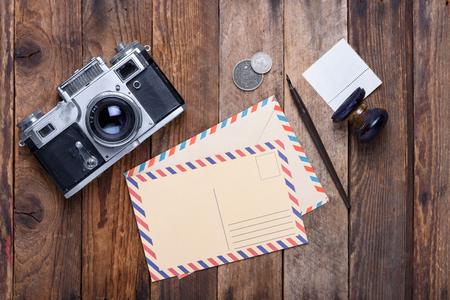 kugelschreiber: Weinlesepostkarte und Umschlag mit Retro-Kamera auf alten Holztisch Lizenzfreie Bilder