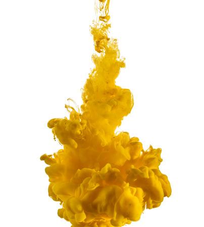 Gele inkt druppel stroomt in het water, op wit wordt geïsoleerd Stockfoto