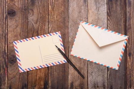 Carte postale avec enveloppe fontaine bout du stylo sur la vieille table en bois