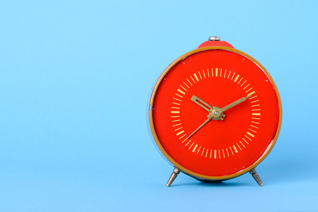 Red retro clock on blue background with copy space