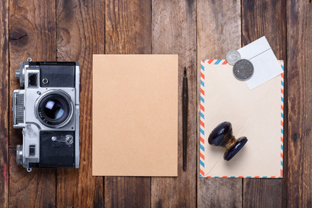 old envelope: Card with envelope, stamps and retro camera on old wooden table Stock Photo