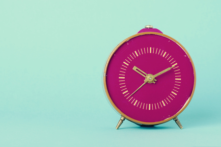 Retro clock on blue background with copy space, vintage toned Banco de Imagens