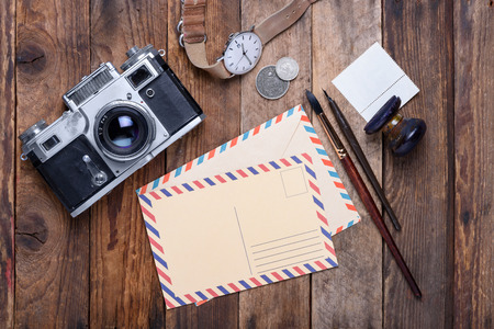 vintage envelope: Blank post card with envelope and vintage camera, stamps, watch, ink pen and brush on wooden table Stock Photo