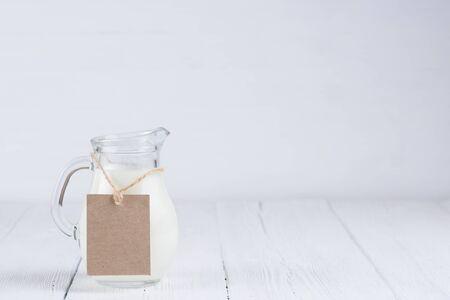 Jarra de leche con etiqueta de papel en blanco en la cuerda en la mesa de madera blanca Bodegón