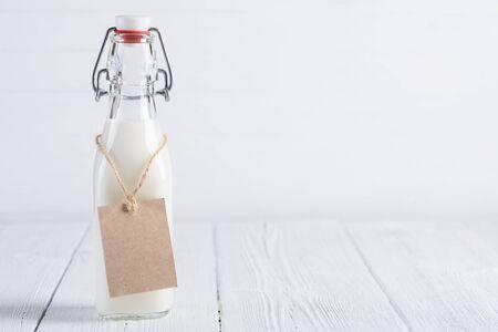 verre de lait: Bouteille de lait avec le blanc étiquette de papier sur la corde sur blanc peint table en bois encore vie