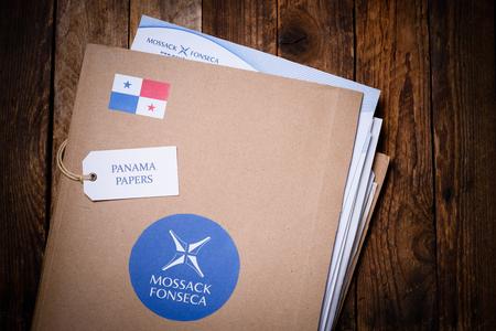 bandera de panama: CRACOVIA, POLONIA - 5 DE ABRIL, 2016: Carpeta con Mossack Fonseca logotipo y los documentos impresos de Mossack Fonseca sitio web de la empresa. Los documentos de Panamá son un conjunto de 11,5 millones de documentos confidenciales filtrados con información detallada miles de empresas en alta mar l