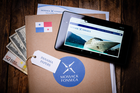bandera de panama: KRAKOW, POLAND - APRIL 5, 2016 : Paper folder with Mossack Fonseca logo with US and EU currency and tablet showing Mossack Fonseca web site. The Panama Papers are set of 11.5 million leaked confidential documents with detailed information thousands offsho Editorial