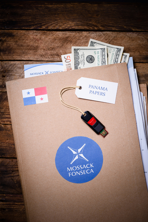 bandera panama: KRAKOW, POLAND - APRIL 5, 2016 : Folder with Mossack Fonseca logo and US and EU currency with flash drive. Panama Papers are millions leaked documents with information about offshore companies.