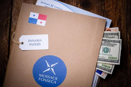 bandera de panama: CRACOVIA, POLONIA - 5 DE ABRIL, 2016: Carpeta con el logotipo de Mossack Fonseca con Estados Unidos y la moneda de la UE. Los documentos de Panamá son un conjunto de 11,5 millones de documentos confidenciales filtrados con información detallada miles de empresas en alta mar listados por Panamá pr servicios corporativos
