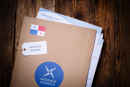 millions: KRAKOW, POLAND - APRIL 5, 2016 : Folder with Mossack Fonseca logo and printed documents from company web site. Panama Papers are millions leaked documents with information about offshore companies.