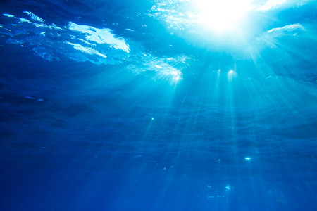 Underwater shot with sunrays in deep blue tropical sea 스톡 콘텐츠