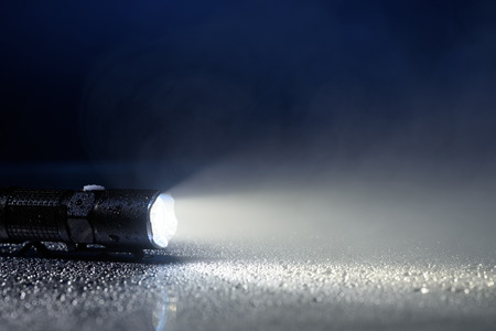 waterproof: Tactical waterproof flashlight with water drops and fog Stock Photo