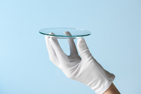 reseach: New features of glass research, hand in glove holding circle piece of transparent material