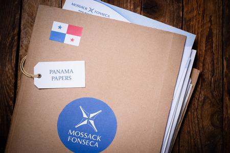 bandera de panama: CRACOVIA, POLONIA - 5 DE ABRIL, 2016: Carpeta con el logotipo de Mossack Fonseca y documentos impresos desde el sitio web de la empresa. Documentos de Panam� son millones filtraron documentos con informaci�n sobre empresas offshore.