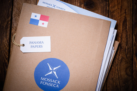 bandera de panama: KRAKOW, POLAND - APRIL 5, 2016 : Folder with Mossack Fonseca logo and printed documents from company web site. Panama Papers are millions leaked documents with information about offshore companies.