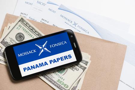 bandera panama: Cracovia, Polonia - ABRIL 6, 2016: Tel�fono con el logotipo de Mossack Fonseca y texto Papeles Panam� y documentos impresos desde el sitio web de Mossack Fonseca, la moneda estadounidense.