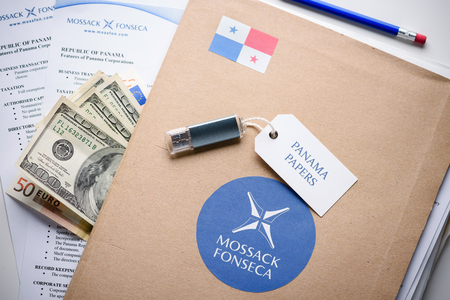 bandera panama: KRAKOW, POLAND - APRIL 5, 2016 : Folder with Mossack Fonseca logo and printed documents from Mossack Fonseca web site, with US and EU currency and flash drive. The Panama Papers are set of 11.5 million leaked confidential documents with detailed informati