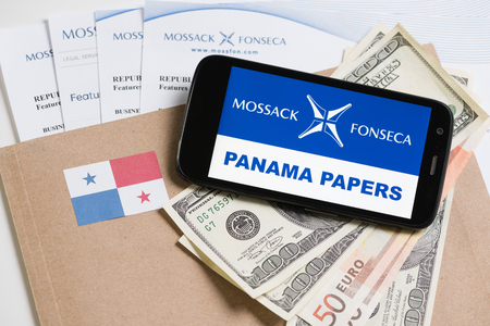 bandera panama: KRAKOW, POLAND - APRIL 6, 2016 : Folder with Mossack Fonseca logo and printed documents from its web site, Panama flag, US and EU currency and phone.