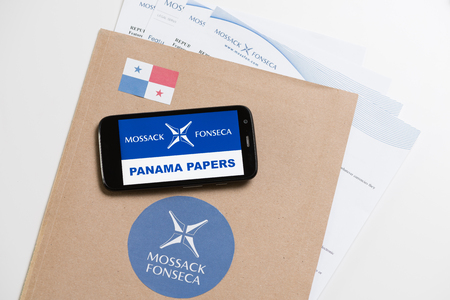 bandera panama: KRAKOW, POLAND - APRIL 6, 2016 : Folder with Mossack Fonseca logo and printed documents from its web site and phone with Mossack Fonseca logo and Panama Papers text.