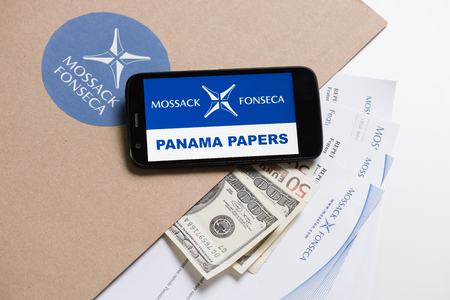bandera de panama: KRAKOW, POLAND - APRIL 6, 2016 : Folder with Mossack Fonseca logo and printed documents from its web site, US and EU currency and phone. Editorial