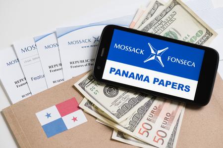 bandera de panama: Cracovia, Polonia - ABRIL 6, 2016: Carpeta con el logotipo de Mossack Fonseca y documentos impresos desde que es el sitio web, la bandera de Panamá, Estados Unidos y la moneda de la UE y el teléfono con el texto de los documentos de Panamá. Editorial
