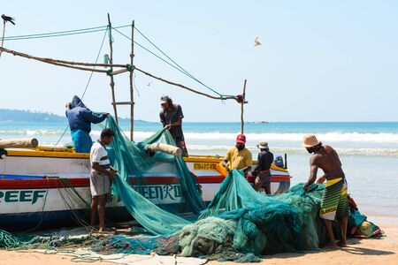 WELIGAMA, SRI LANKA - MARCH 3, 2016: Group local of fishermens reviewing and folding fishing nets near the traditional wooden boat on the ocean beach at sunny day