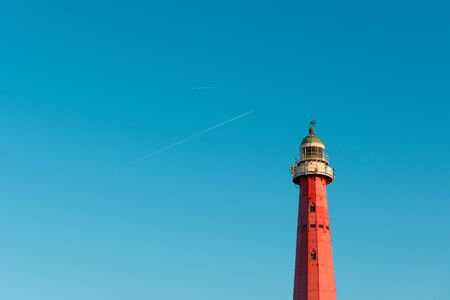 Vintage red iron lighthouse over blue sky background with airplane traces and copy space