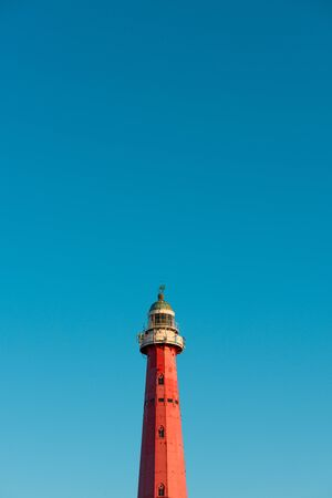 Lighthouse over blue sky background with copy space
