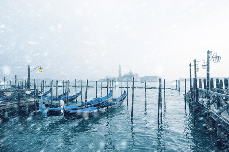 Traditional Italian gondolas moored to the poles in Europe Venice near the city center and Saint Mark square with a backgound view of the church of San Giorgio Maggiore at cold windy snowy winter day