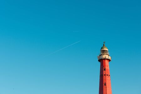 Lighthouse over blue sky background with airplane traces and copy space