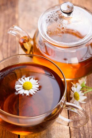 chamomile tea: Herbal chamomile tea in glass cup and teapot with chamomile flowers on wooden table still life