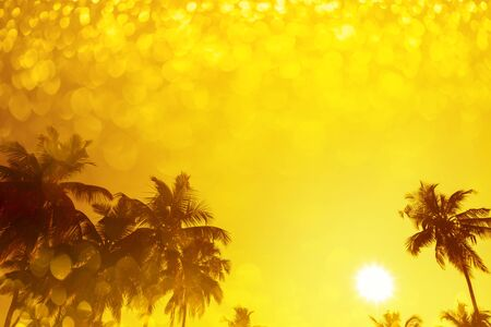 Palm trees silhouettes on tropical beach at summer warm vivid sunset with party shiny glitter overlay effect