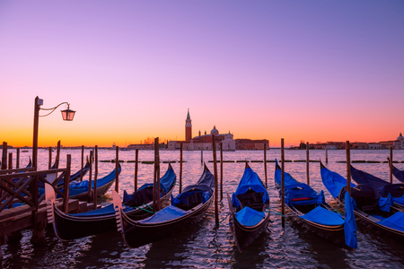 saint mark's: Traditional Italian gondolas moored to the poles in Europe Venice near the city center and Saint Mark square with a background view of the church of San Giorgio Maggiore at sunrise Stock Photo