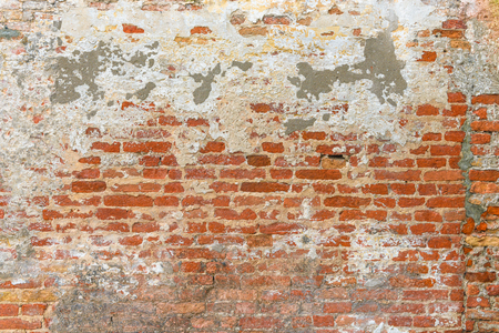Old brick wall texture, covered with multiply stucco plaster and paint layers, weathered and distressed