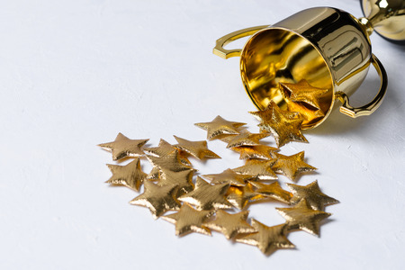 Golden trophy cup with golden stars on white textured background Stock Photo