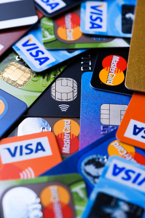 Krakow, Poland - June 16, 2017: Plastic bank payment cards, Visa and Mastercard, credit and debit with different chips and wireless payment technology. Редакционное