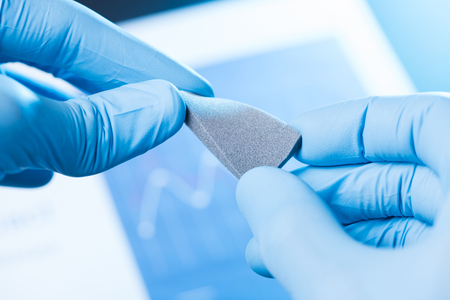 Scientist hand in gloves hold and bend small piece of gray porous foam, new type of material with different properties research concept Banco de Imagens