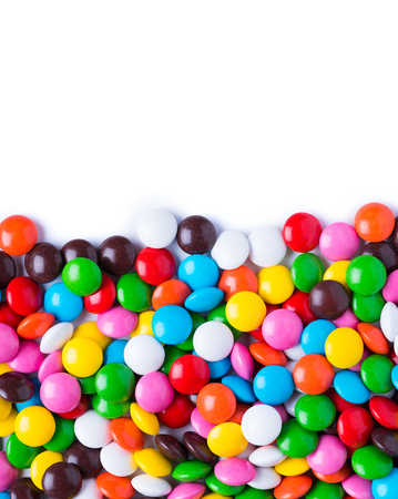 Vibrant colorful small circle candies border on white background Stock Photo