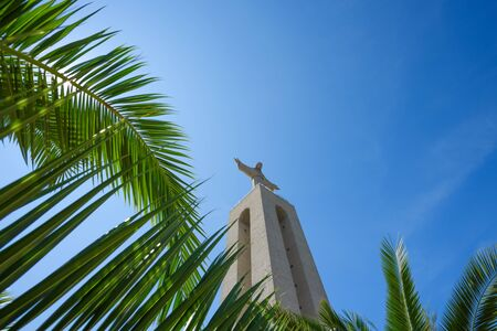 Christ the King Statue through green palm leafs at clear summer sunny day in Lisbon Portugal