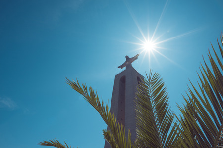 Christ the King Statue through green palm leaf at clear summer sunny day in Lisbon Portugal vintage color toned Editorial