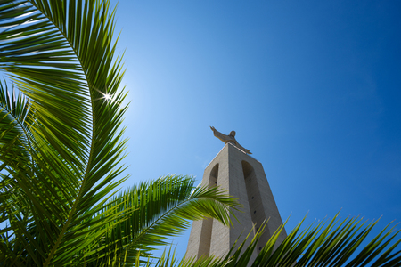Christ the King Statue through green palm leaf at clear summer sunny day in Lisbon Portugal Editorial