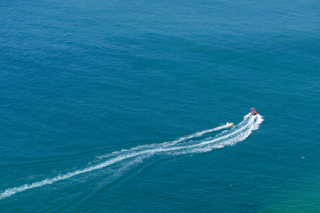 Tourists taking ride by speed boat on rubber tube boat on waves in ocean, aerial view