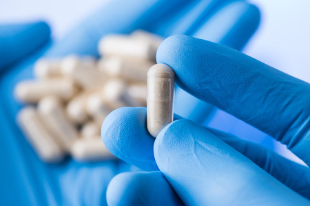 Scientist hands in gloves hold pills, new pill research concept