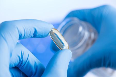 Transparent liquid supplement in capsule in scientist hands