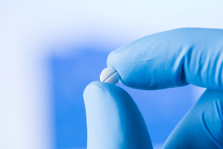 Small pill in the scientist fingers in gloves, medical research concept
